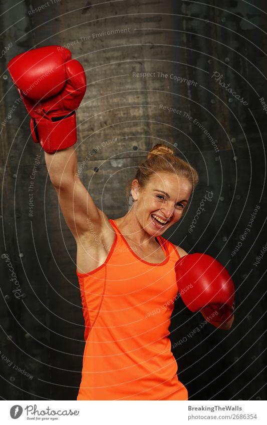 Frontalporträt einer jungen erwachsenen Frau in roten Boxhandschuhen mit der Geste des Siegers oder Champions in der Hand, lächelnd und in die Kamera blickend