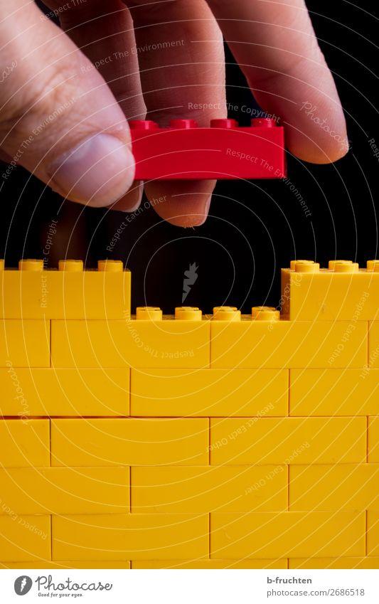 Spiel-Bausteine, gelbe Mauer, roter Baustein in der Hand Spielen Modellbau Hausbau Renovieren Handwerker Baustelle Finger Spielzeug Kunststoff