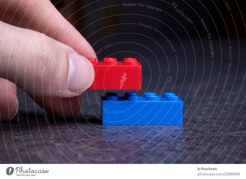 Zwei Spielzeug-Bausteine aneinander setzen Finger Kunststoff Zeichen wählen berühren festhalten Spielen blau rot Liebe Treue Beginn Kreativität paarweise
