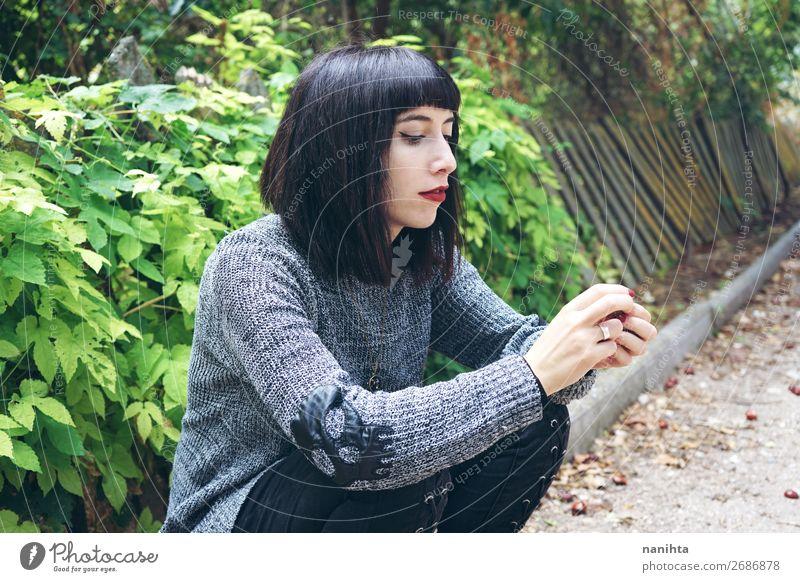 Brünette Frau, die auf dem Boden in einem Park sitzt. Lifestyle Stil Glück schön Erholung ruhig Mensch feminin Junge Frau Jugendliche Erwachsene 1 18-30 Jahre