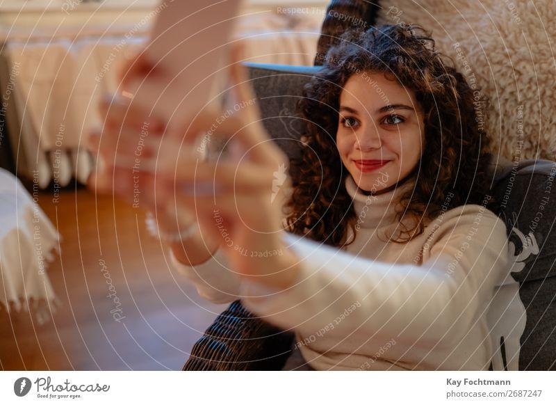 junge Frau nimmt eine Selbstgefälligkeit attraktiv schön Bluse Brasilianer braunhaarig Fotokamera Kaukasier Funktelefon heiter gemütlich lockig krause Haare