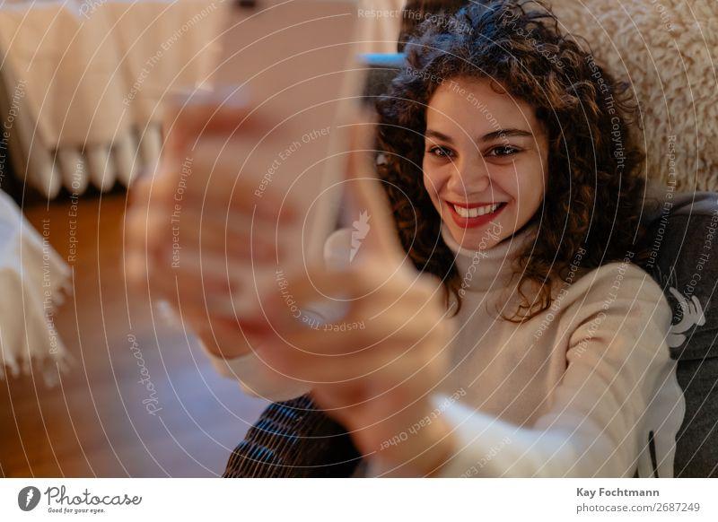 fröhliche Frau nimmt sich eine Selbstgefälligkeit attraktiv schön Bluse Brasilianer braunhaarig Fotokamera Kaukasier Funktelefon heiter gemütlich lockig