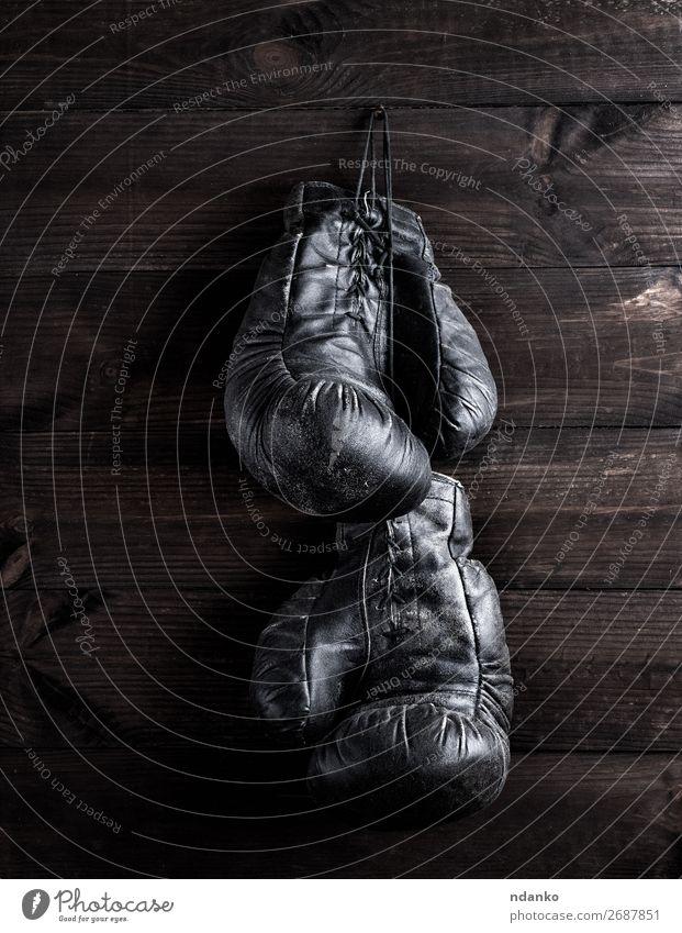 schwarze Boxhandschuhe aus Leder, die an einem Nagel hängen. Lifestyle Fitness Sport Seil Handschuhe Holz alt retro braun Schutz Konkurrenz Kraft Aktion antik