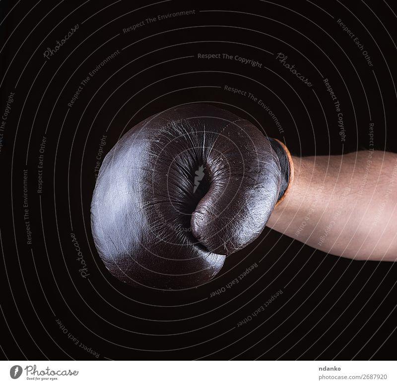brauner Boxhandschuh angezogen auf der Männerhand Sport Erfolg Hand Leder Handschuhe alt Fitness dreckig dunkel schwarz Kraft Schutz Konkurrenz Kasten Boxer