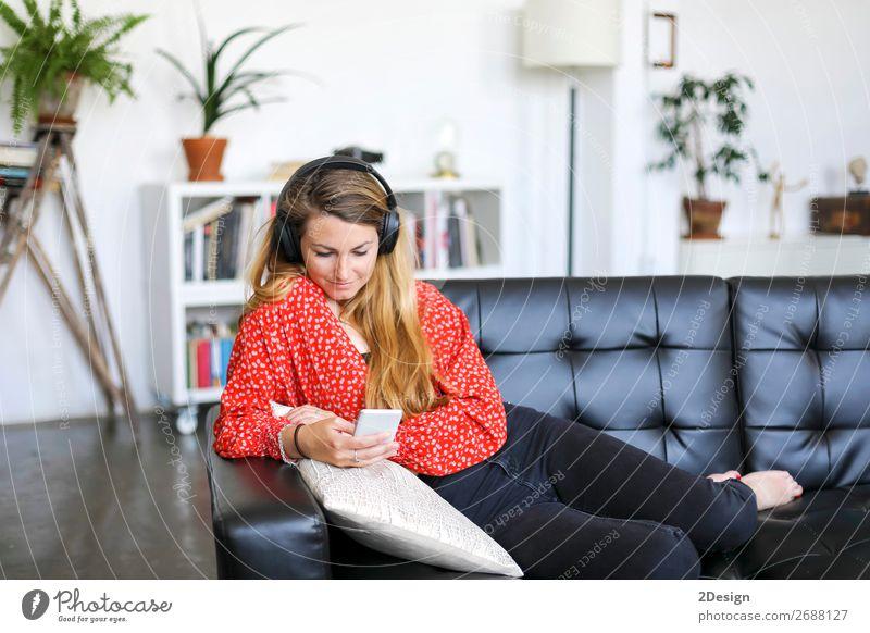 Junge Frau benutzt ein Smartphone und hört Musik. Lifestyle Freude Glück schön Haare & Frisuren Erholung ruhig Freizeit & Hobby Spielen Sofa Telefon Handy PDA