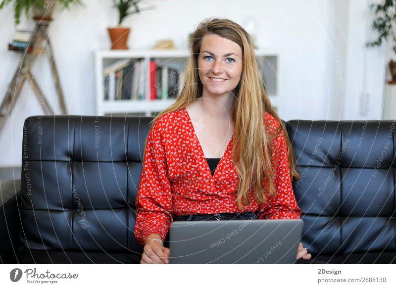 Lächelnde Frau, die zu Hause auf einem Sofa sitzt und einen Laptop benutzt. kaufen Glück schön Schule lernen Studium Arbeit & Erwerbstätigkeit Computer Notebook