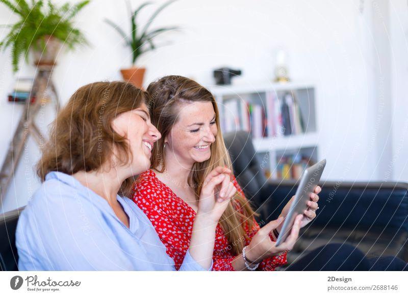 Frauen zu Hause sitzen auf dem Sofa und benutzen einen Tablet-PC. Lifestyle Freude Glück schön Erholung Wohnung sprechen Computer Technik & Technologie Internet