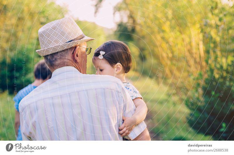 Rückansicht des älteren Mannes, der das Mädchen in den Armen hält. Lifestyle Glück Erholung Sommer Kind Mensch Baby Kleinkind Frau Erwachsene Eltern Großvater