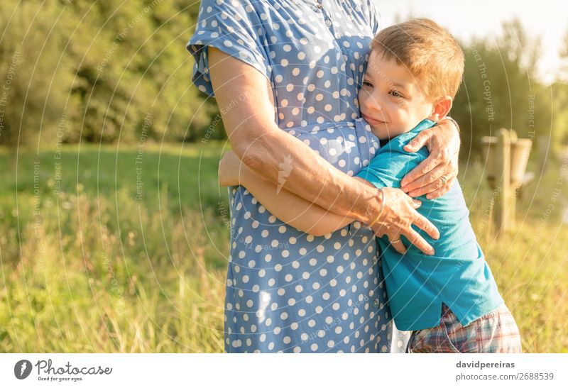 Glücklicher Enkel, der seine Großmutter im Freien umarmt. Lifestyle Erholung Freizeit & Hobby Sommer Garten Kind Mensch Junge Frau Erwachsene Mann Eltern