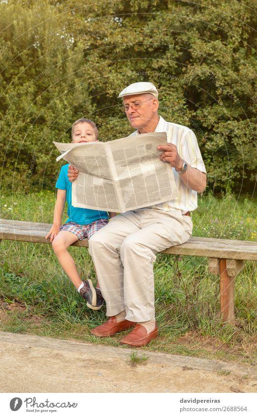 Senior Mann und gelangweiltes Kind lesen Zeitung im Freien Lifestyle Glück Erholung Freizeit & Hobby Schule Mensch Junge Erwachsene Eltern Großvater