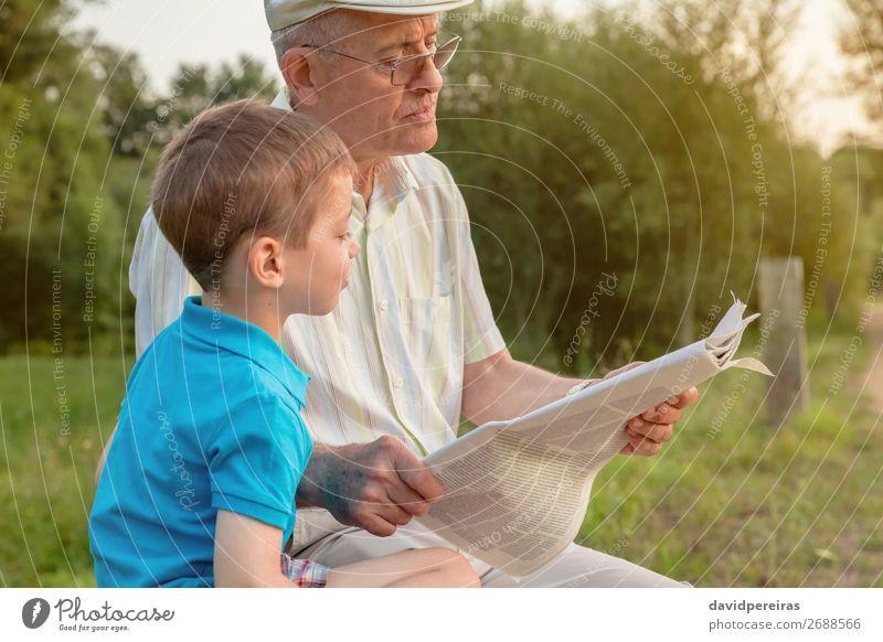 Senior Mann und Kind lesen eine Zeitung im Freien. Lifestyle Glück Erholung Freizeit & Hobby Schule Mensch Junge Erwachsene Eltern Großvater
