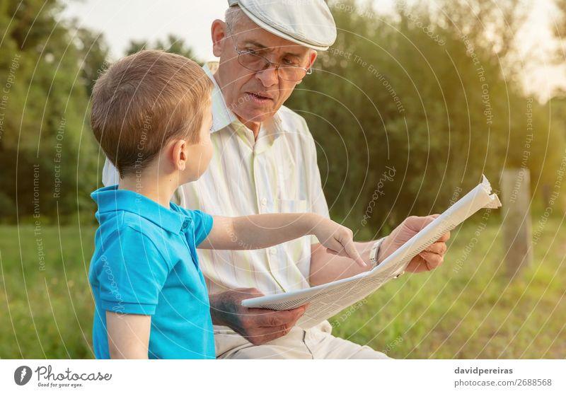 Senior Mann und Kind lesen eine Zeitung im Freien. Lifestyle Glück Freizeit & Hobby Schule Mensch Junge Erwachsene Eltern Großvater Familie & Verwandtschaft