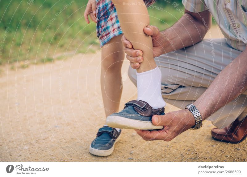 Großvater legt seinem Enkel den Schuh im Freien an. Lifestyle Freizeit & Hobby Sommer Garten Kind Mensch Junge Mann Erwachsene Eltern Familie & Verwandtschaft
