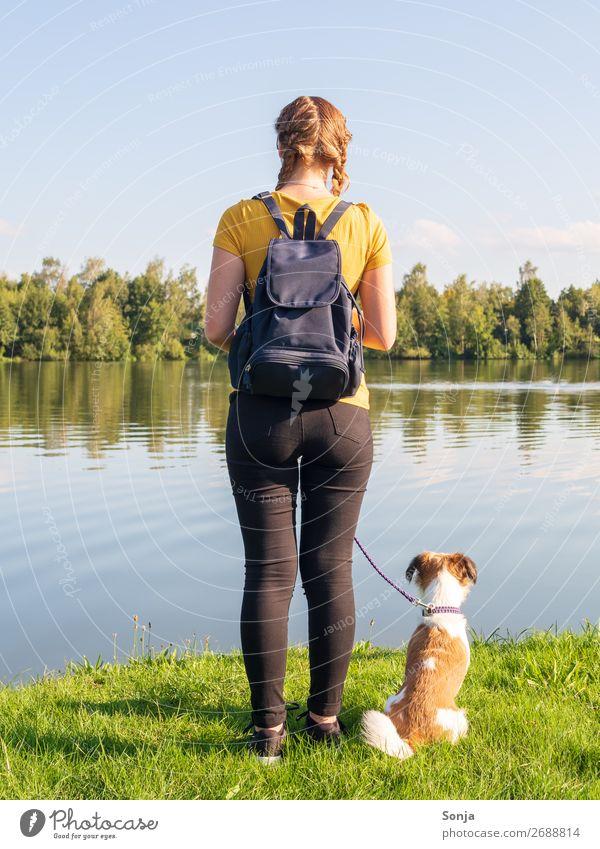 Junge Frau mit kleinen Hund am See Lifestyle Sommer wandern Mensch feminin Jugendliche 1 18-30 Jahre Erwachsene T-Shirt Jeanshose Zopf Tier Rucksack beobachten