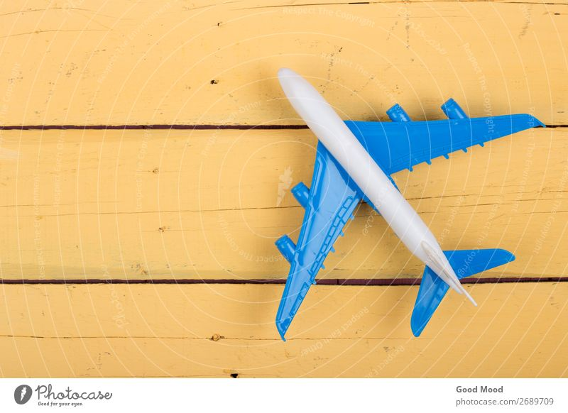 Kind Ferien & Urlaub & Reisen blau Freude Holz gelb lustig klein Textfreiraum Spielen Ausflug Freizeit & Hobby Verkehr Tisch Flugzeug Spielzeug