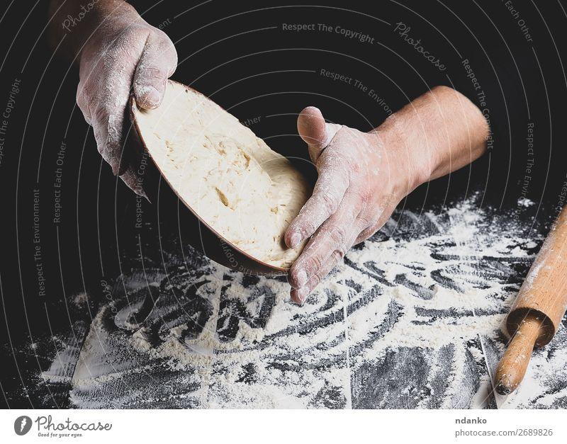 männliche Hand, die eine Keramikplatte mit Hefeteig hält. Teigwaren Backwaren Brot Ernährung Teller Tisch Küche Koch Mann Erwachsene Holz machen frisch schwarz