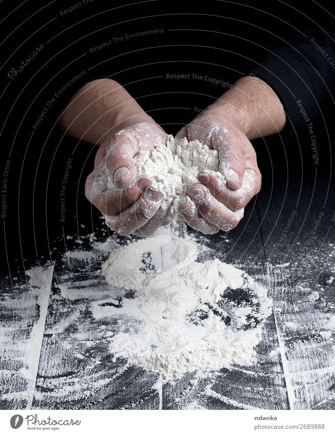 weißes Weizenmehl in männlichen Händen Teigwaren Backwaren Brot Tisch Küche Beruf Koch Mensch Mann Erwachsene Hand Holz machen dunkel schwarz Bäckerei