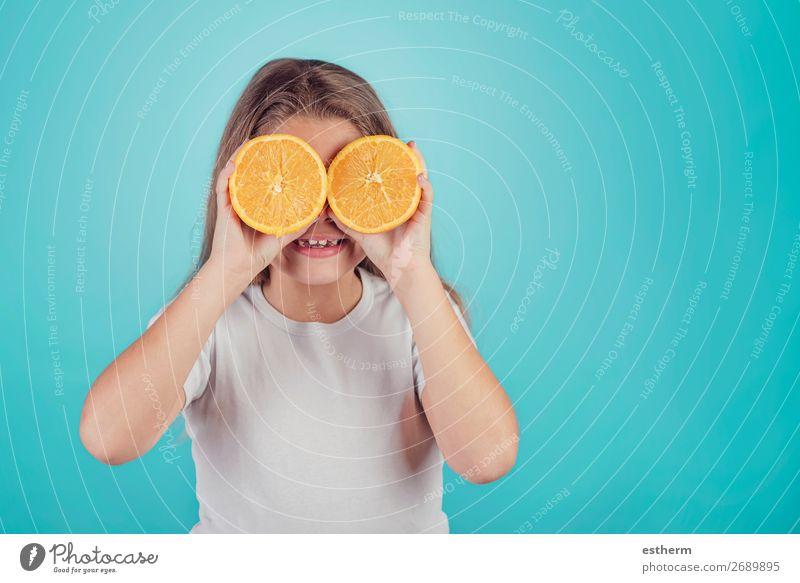 lächelndes kleines Mädchen, das Orangen über den Augen hält. Frucht Dessert Ernährung Mittagessen Vegetarische Ernährung Diät Saft Lifestyle Freude Mensch