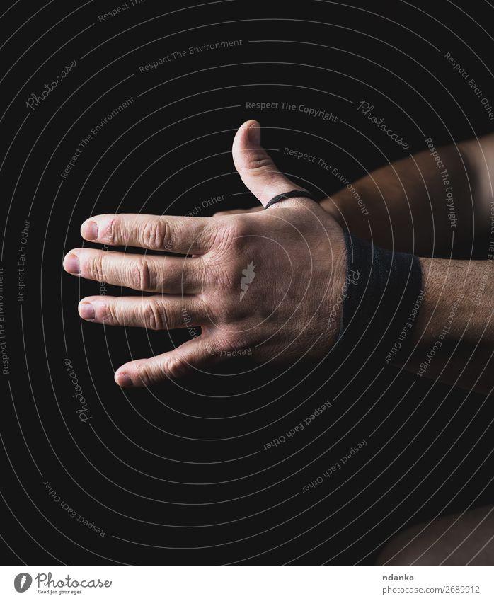 Der Mann wickelt seine Hände in eine schwarze Textilbinde. Lifestyle Haut Fitness Sport Mensch Erwachsene Arme Hand 1 30-45 Jahre drehen Aggression dunkel stark
