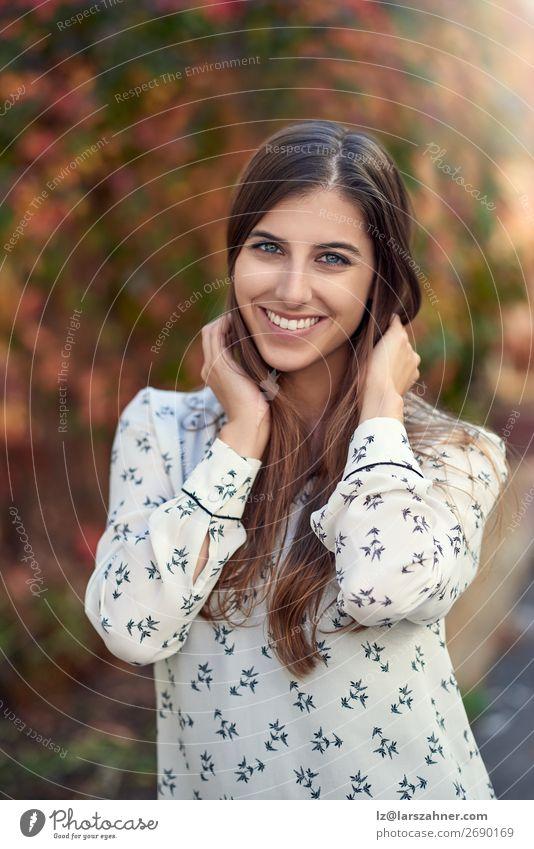 Attraktive junge Frau in einer bunten Herbststraße Glück Erwachsene Blatt Straße Mode brünett Lächeln lachen Fröhlichkeit klug attraktiv fallen Wange modisch