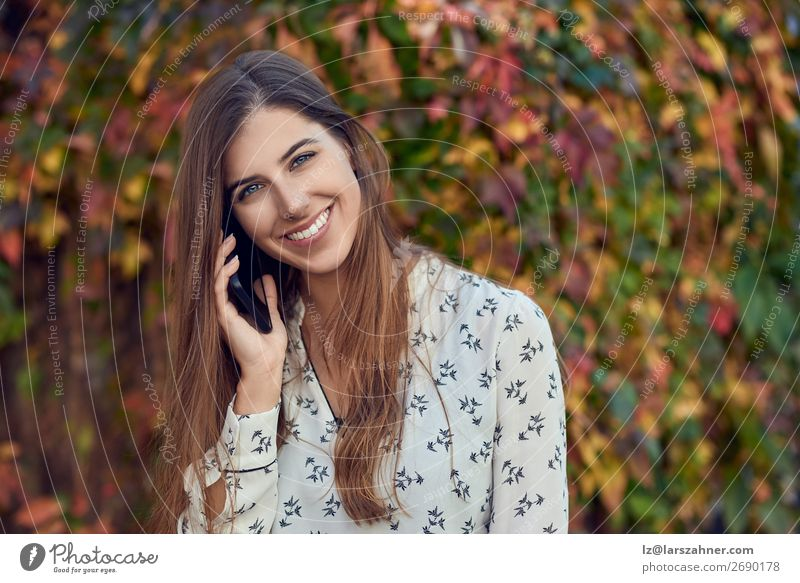 Lächelnde junge Frau, die im Herbst auf einem Handy plaudert. Glück Gesicht Sommer Business Telefon PDA Erwachsene 1 Mensch 18-30 Jahre Jugendliche Blatt Straße