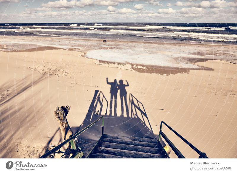 Silhouetten eines Paares, das an einem Strand winkt. Lifestyle Freude Glück Ferien & Urlaub & Reisen Ausflug Meer Winter Hochzeit Mensch Geschwister