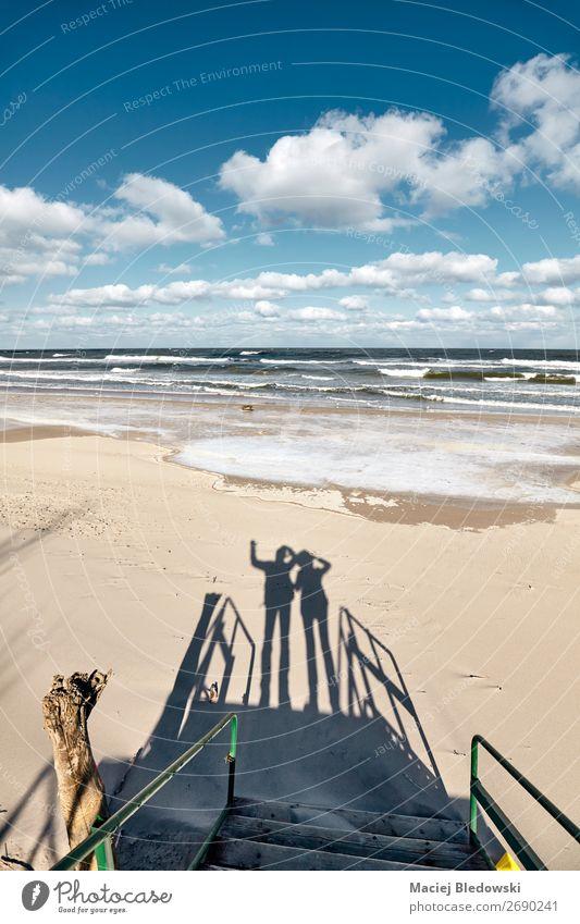 Silhouetten eines Paares, das an einem Strand winkt. Lifestyle Freude Ferien & Urlaub & Reisen Abenteuer Meer Winter Winterurlaub wandern Hochzeit Mensch