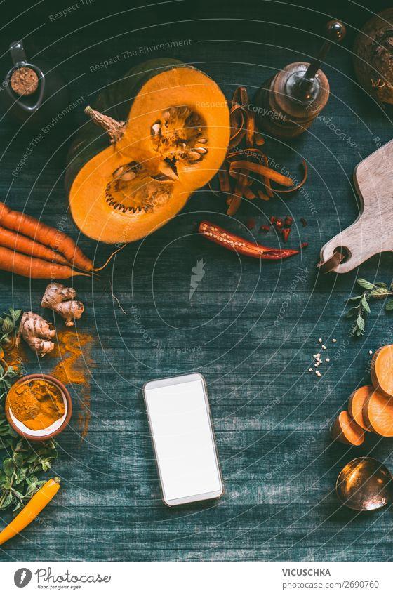 Smartphone auf Küchentisch mit Kürbis Gesunde Ernährung Foodfotografie Lebensmittel Hintergrundbild Herbst Design Tisch kaufen Gemüse Internet Handy