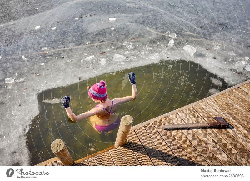 Fit Frau führt Eisschwimmen im Eisloch durch. Lifestyle Körper Freizeit & Hobby Abenteuer Winter Winterurlaub Sport Wintersport Schwimmen & Baden Mensch