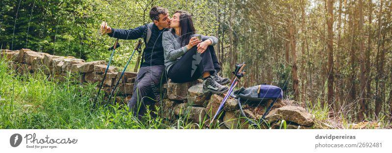 Ein Paar küsst sich, während man eine Pause macht, um Trekking zu machen. Essen trinken Lifestyle Freizeit & Hobby Abenteuer Berge u. Gebirge wandern Sport