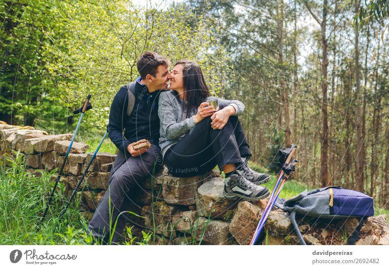 Ein Paar, das sich küssen will, während es eine Pause macht, um Trekking zu machen. Essen trinken Lifestyle Freizeit & Hobby Abenteuer Berge u. Gebirge wandern