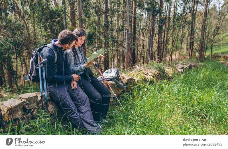 Ein Paar beim Trekking, das auf eine Karte schaut. Freizeit & Hobby Ausflug Abenteuer Sightseeing Berge u. Gebirge wandern Sport Mensch Frau Erwachsene Mann