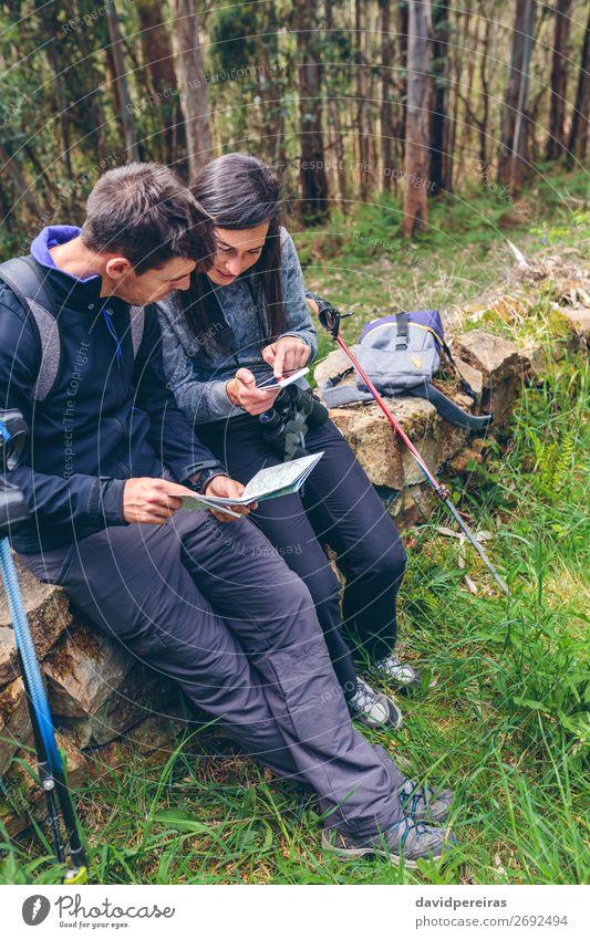 Ein Paar beim Trekking im Sitzen, das mobil aussieht und eine Karte hat. Ausflug Abenteuer Sightseeing Berge u. Gebirge wandern Sport PDA Mensch Frau Erwachsene