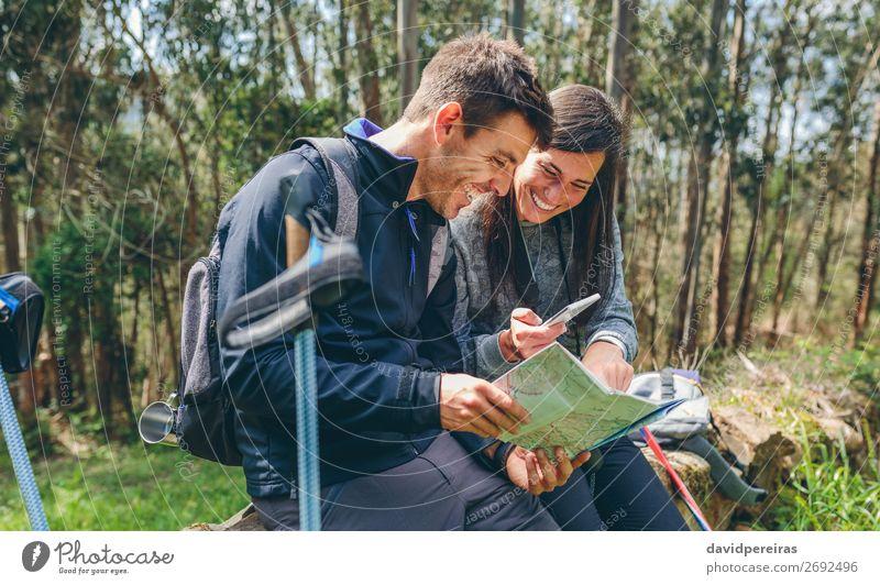 Ein Paar beim Trekking im Sitzen, das mobil aussieht und eine Karte hat. Freude Glück Ausflug Abenteuer Sightseeing Berge u. Gebirge wandern Sport PDA Mensch