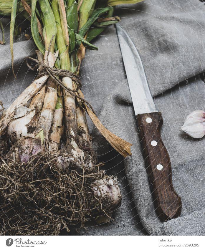 junger Knoblauch in einem Bündel gebunden Gemüse Kräuter & Gewürze Ernährung Vegetarische Ernährung Messer Tisch Natur Pflanze Blatt Holz frisch natürlich braun