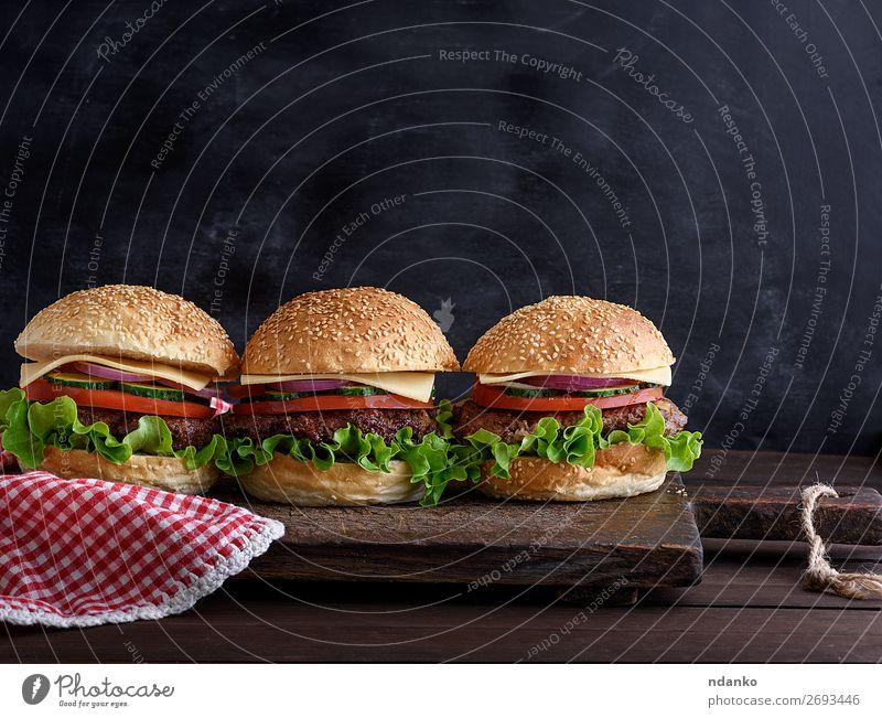 drei Hamburger mit Gemüse Fleisch Käse Brot Brötchen Mittagessen Abendessen Fastfood Tisch Tafel Holz dunkel frisch schwarz Salatbeilage Amerikaner Hintergrund