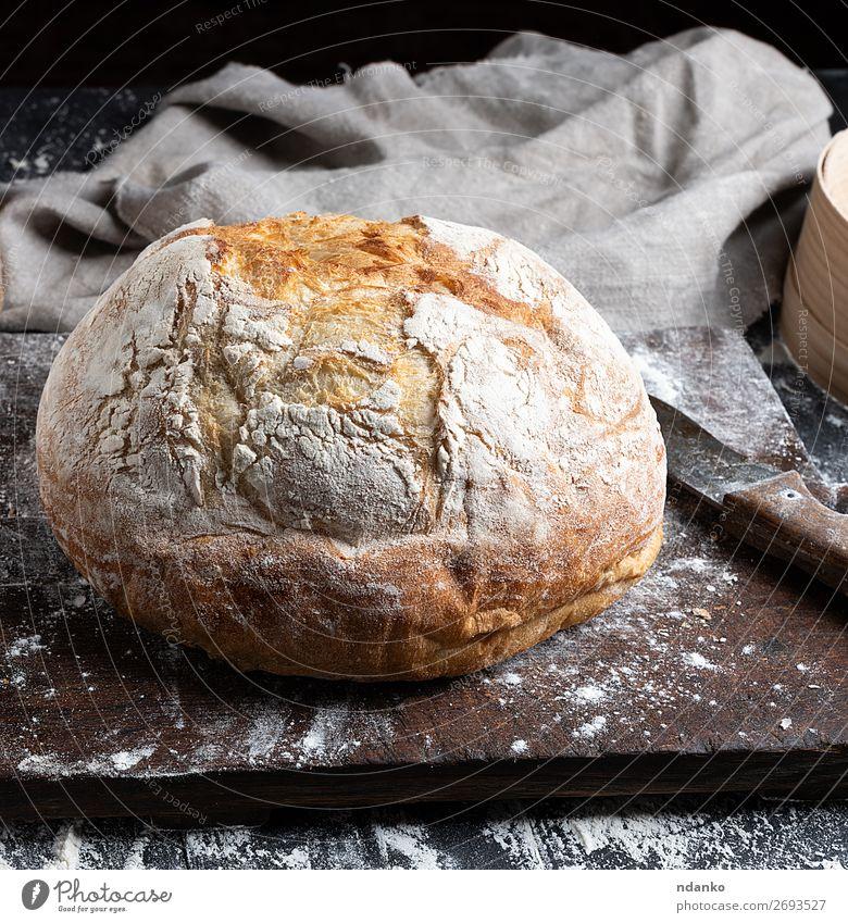 ganzes gebackenes Rundbrot Brot Ernährung Messer Tisch Küche Holz machen dunkel frisch braun schwarz weiß Tradition Bäckerei Holzplatte Essen zubereiten