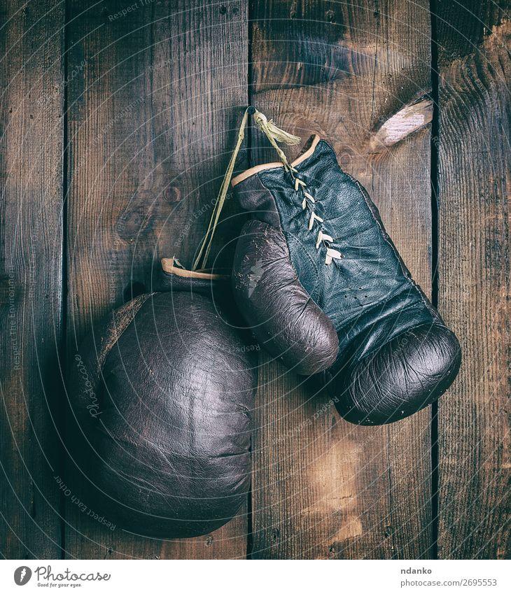 Boxhandschuhe aus Leder, die an einem Nagel hängen. Lifestyle Fitness Sport Seil Handschuhe Holz alt dreckig retro braun schwarz Schutz Idee Konkurrenz