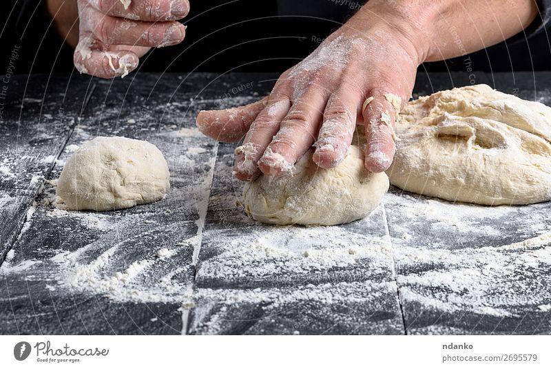 kochen und Teigkugeln auf einem schwarzen Holztisch zubereiten. Teigwaren Backwaren Brot Ernährung Haut Tisch Küche Koch Mensch Mann Erwachsene Hand machen weiß