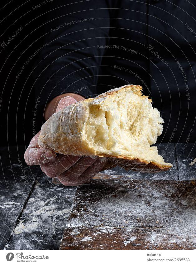 Chefkoch hält halbgebackenes weißes Weizenmehlbrot in der Hand. Brot Ernährung Tisch Küche Mensch Finger Holz machen dunkel frisch braun schwarz Tradition
