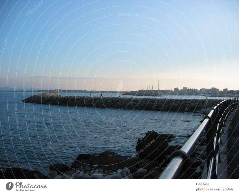 Blick zur Hafenmauer Mauer Anlegestelle Licht Belichtung Dämmerung Meer Spanien Wasser Stein Bruchstück Felsen Sonne Estartit Himmel blau Geländer Metall Bucht