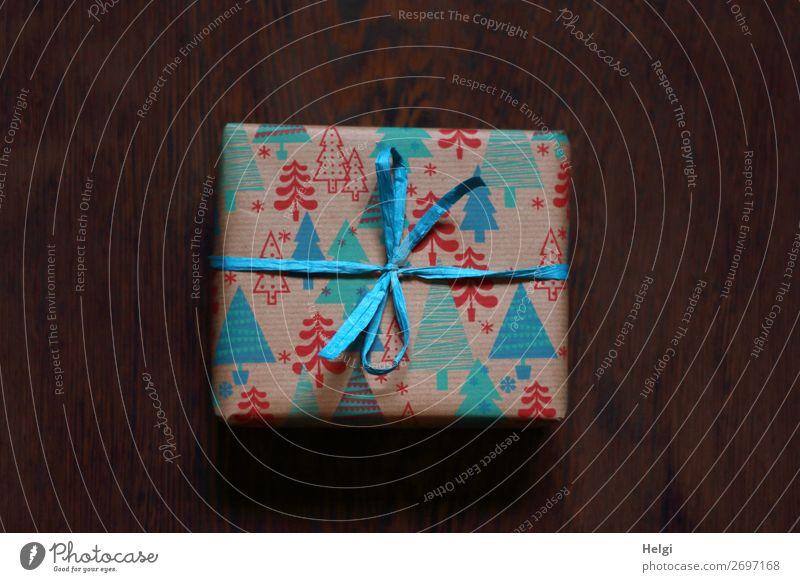 kleines Päckchen als Geschenk verpackt in rot-blau-türkisem  Papier mit Weihnachtsmotiven und türkisfabener Bastschleife Zettel Verpackung