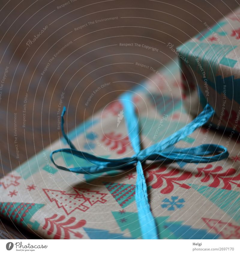 Detailaufnahme eines verpackten Geschenks in Weihnachtspapier mit Band und Schleife aus Bast Feste & Feiern Weihnachten & Advent Dekoration & Verzierung