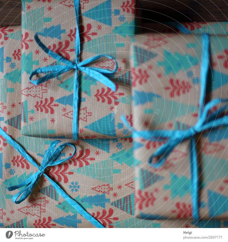 drei verpackte Geschenke in türkis-rot-gemustertem Weihnachtspapier mit türkisfarbenen Bastschleifen Weihnachten & Advent Verpackung Dekoration & Verzierung