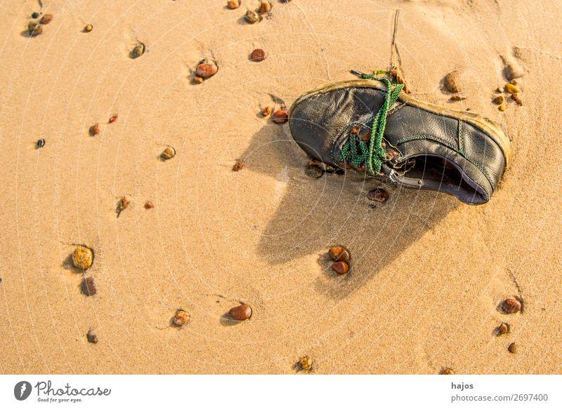alter, verlorener Schuh am Strand Sommer Sand Sonne Ostsee braun Traurigkeit Sandstrand Fund Steine Kiesel Stilleben Urlaub Farbfoto Außenaufnahme Menschenleer