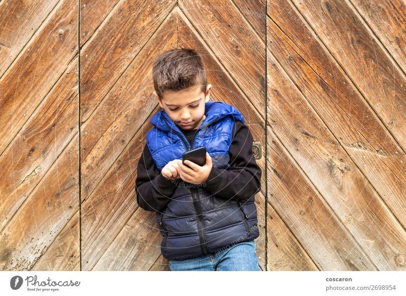 Kleiner Junge mit einem beweglichen Telefon mit einem Hintergrund aus Holztüren. Lifestyle schön Spielen Ferien & Urlaub & Reisen Haus Kind Handy PDA