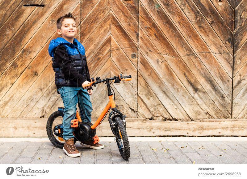 Kleiner Junge mit Fahrrad auf Holztürhintergrund Lifestyle Freude Glück schön Gesicht Freizeit & Hobby Spielen Ferien & Urlaub & Reisen Ausflug Städtereise Haus