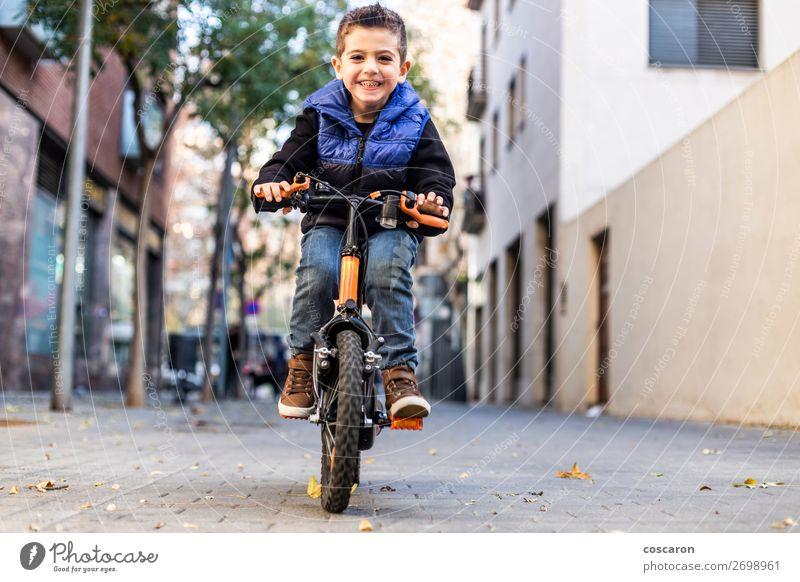 Kleines Kind fährt mit dem Fahrrad auf der Stadtstraße. Lifestyle Freude Glück schön Gesicht Erholung Freizeit & Hobby Spielen Kinderspiel Sommer Sonne Sport