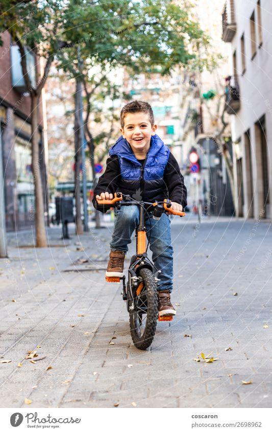 Kleines Kind fährt mit dem Fahrrad auf der Stadtstraße. Lifestyle Freude Glück schön Erholung Freizeit & Hobby Spielen Kinderspiel Sonne Winter Sport