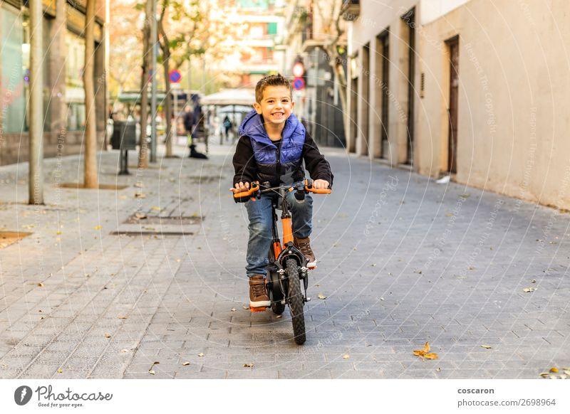 Kleines Kind fährt mit dem Fahrrad auf der Stadtstraße. Lifestyle Freude Glück schön Gesicht Erholung Freizeit & Hobby Spielen Sonne Winter Sport Erfolg